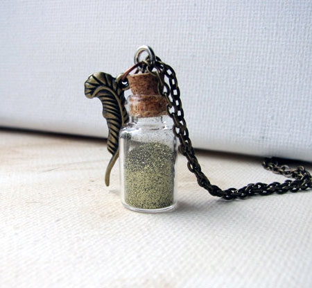 Gold Glitter Dust In A Glass Vial With A Brass Feather Charm Pendant
